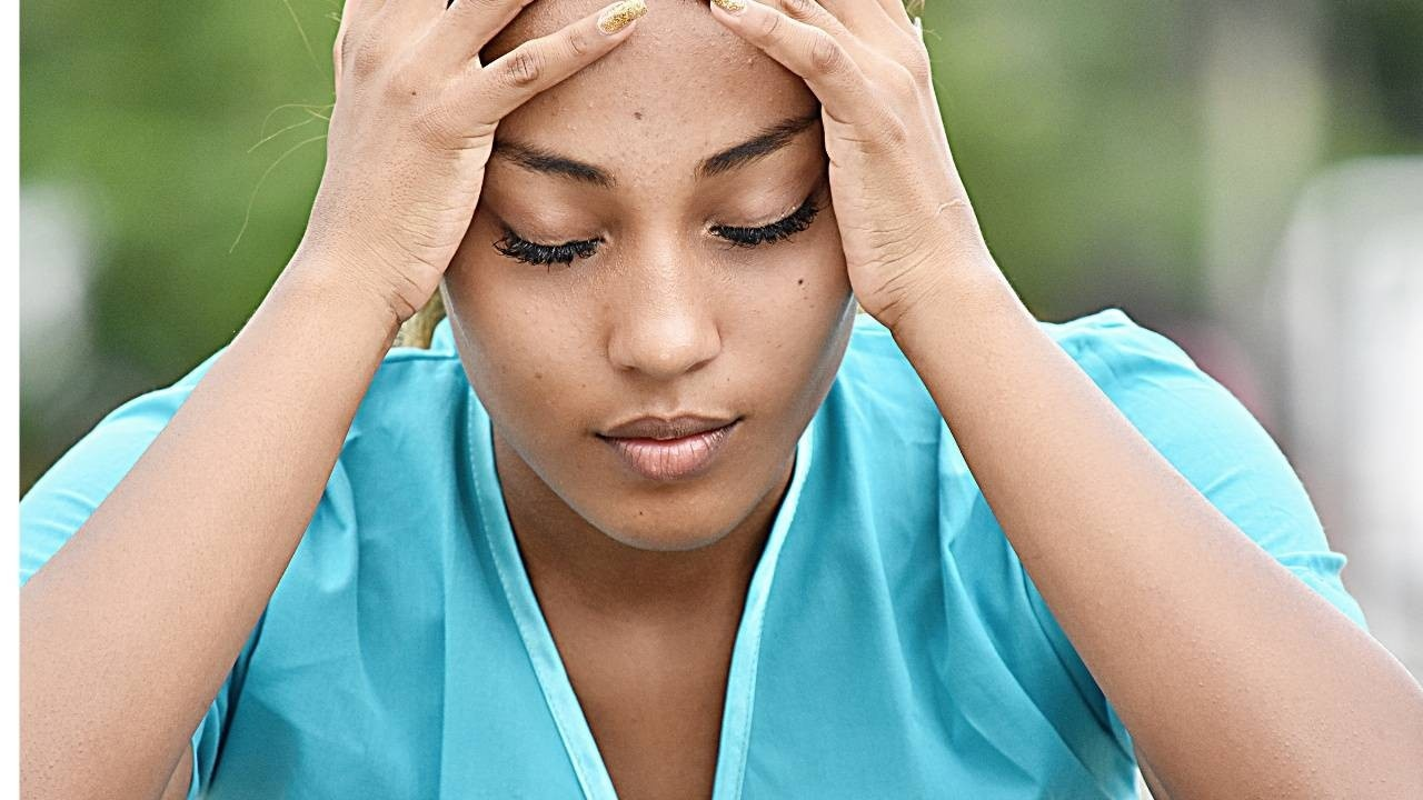 woman with stress and worry holding her head