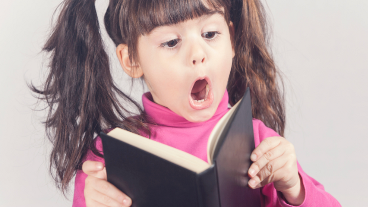 a young girl of about 6 years with brunette hair and  pigtails reading a book and looking astounded by what she reads. She's wearing a pink sweater.