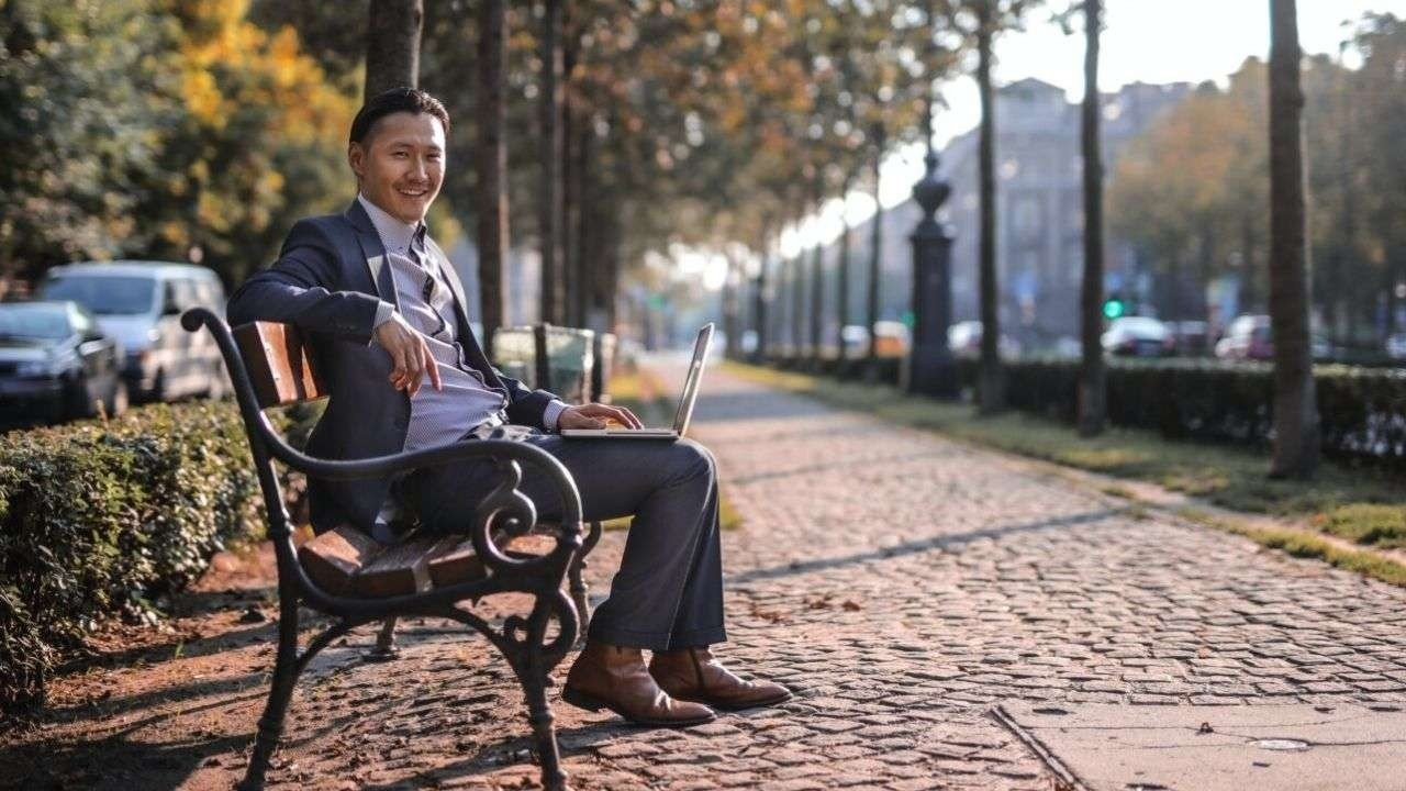 Man with laptop sitting in a park bench