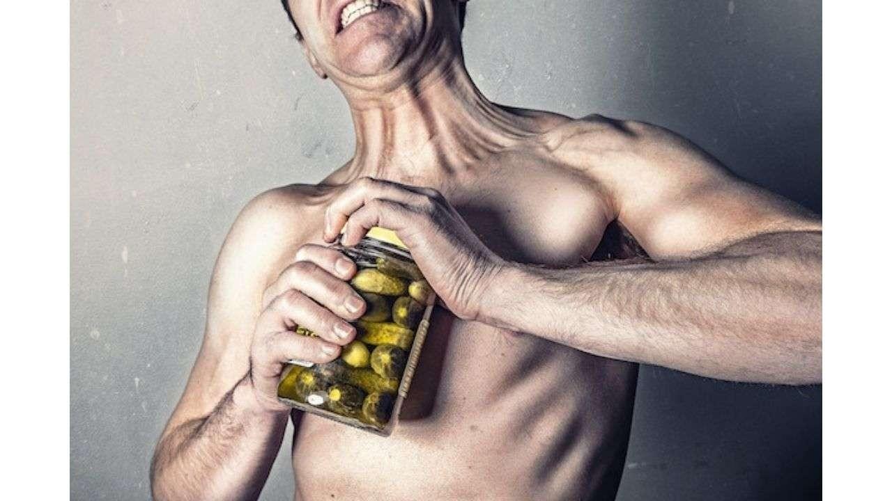 Man opening a pickle bottle