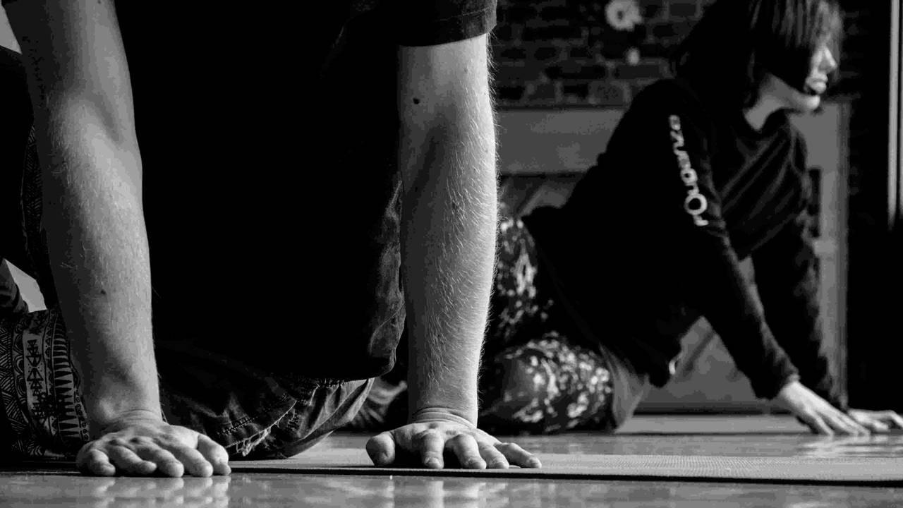 Im Vordergrund stütz eine Person auf beiden Händen, die Hände haben klaren Kontakt und tragen Gewicht. Der Fokus liegt auf den Armen und Händen. Im Hintergrund eine Person in Bewegung. Der Kontkt der rechten Hand sanft am Boden, die linke Hand im Stütz.