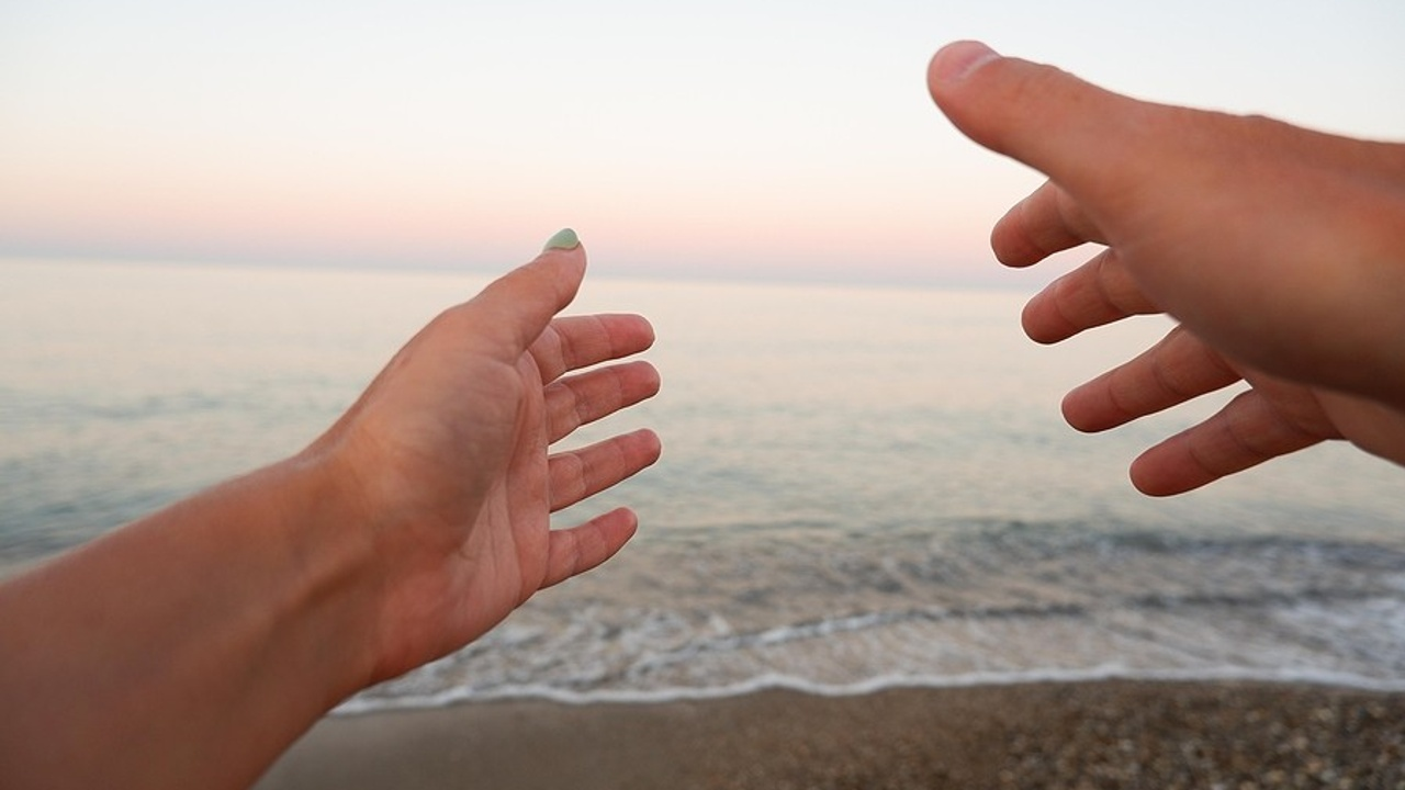 Hand reaches for sunset