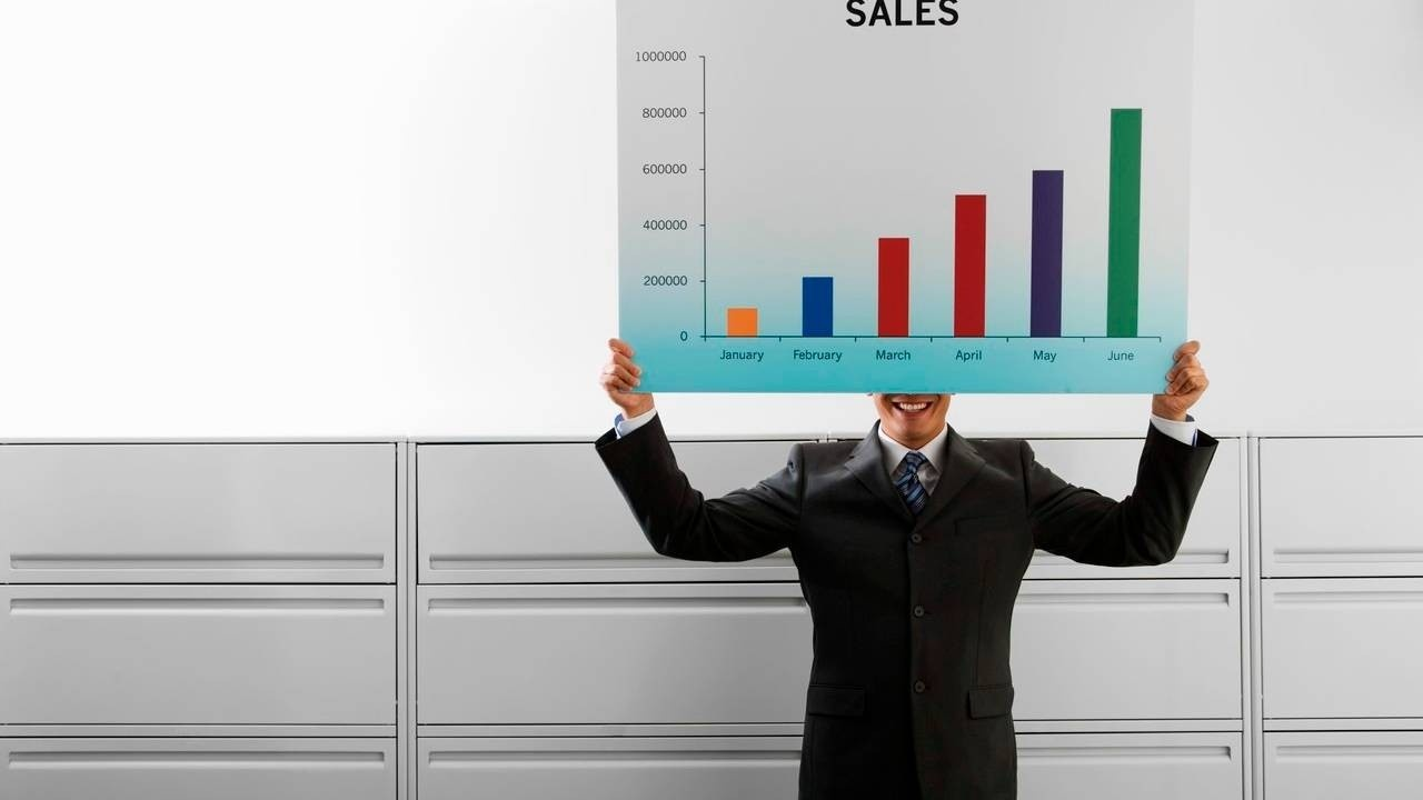 accountant holding up a sales chart