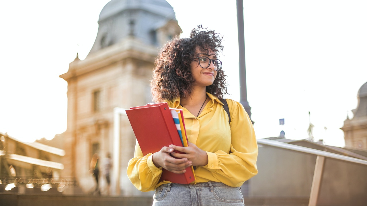 Woman holding books on a college campus