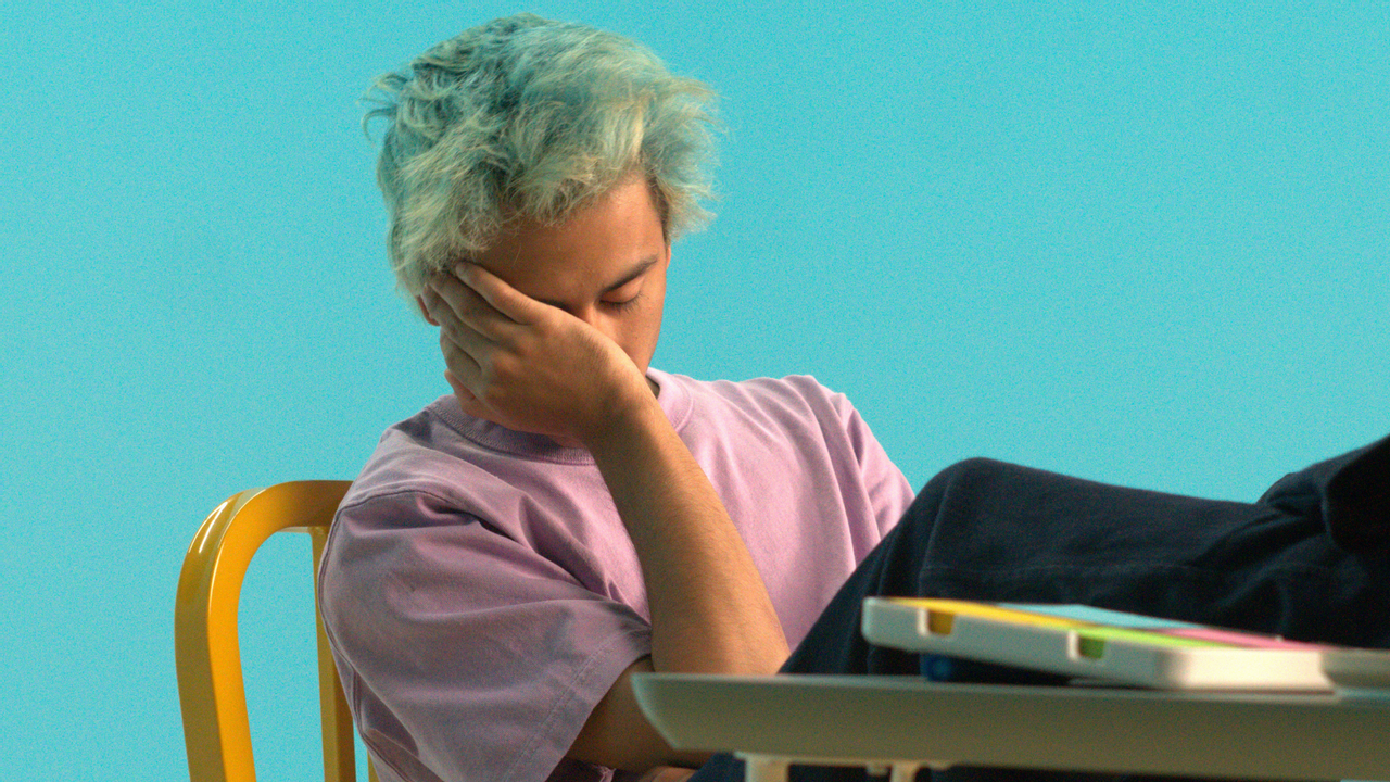 Person slouching with their hand over their face while sitting at a desk