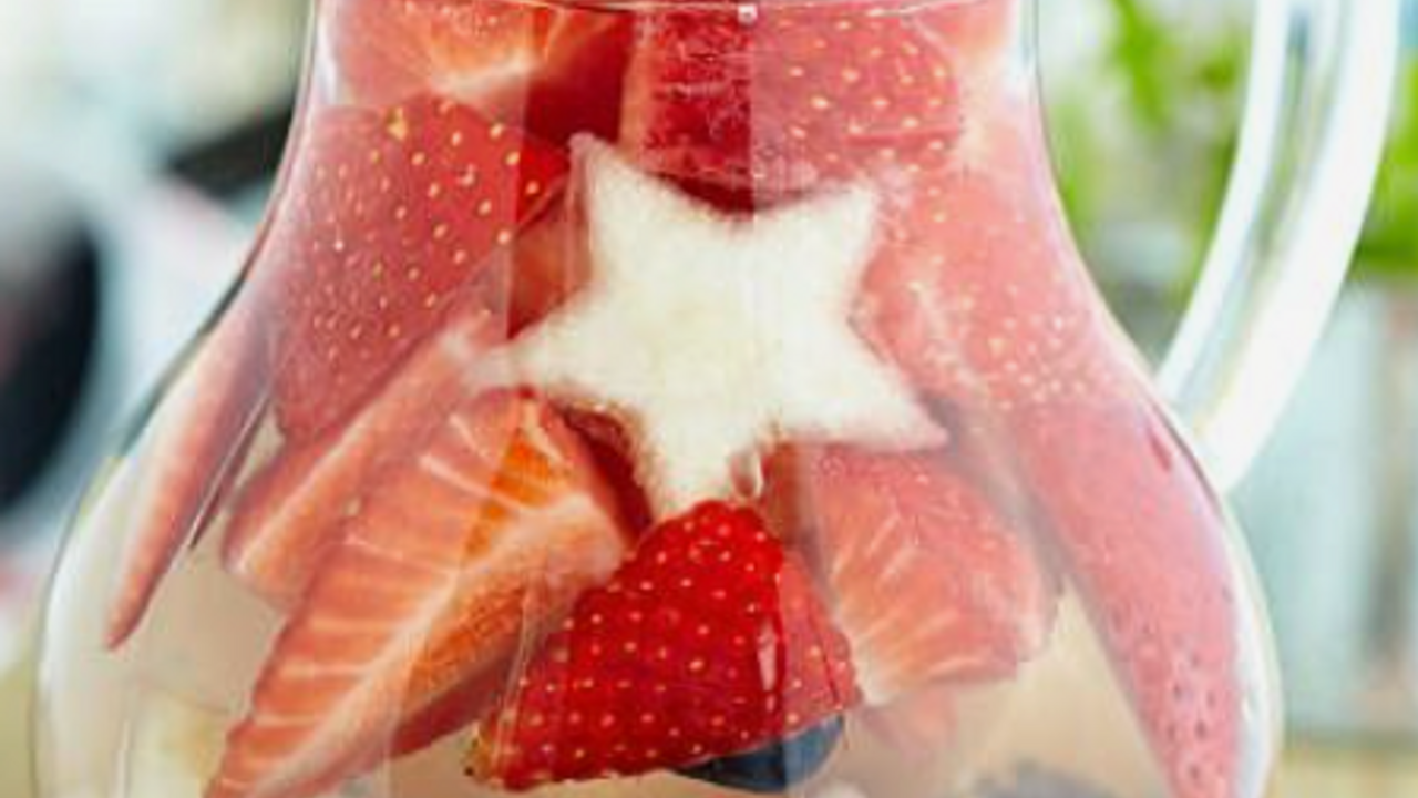 sangria, starfruit, strawberries, blueberries with clear mixers in a glass pitcher