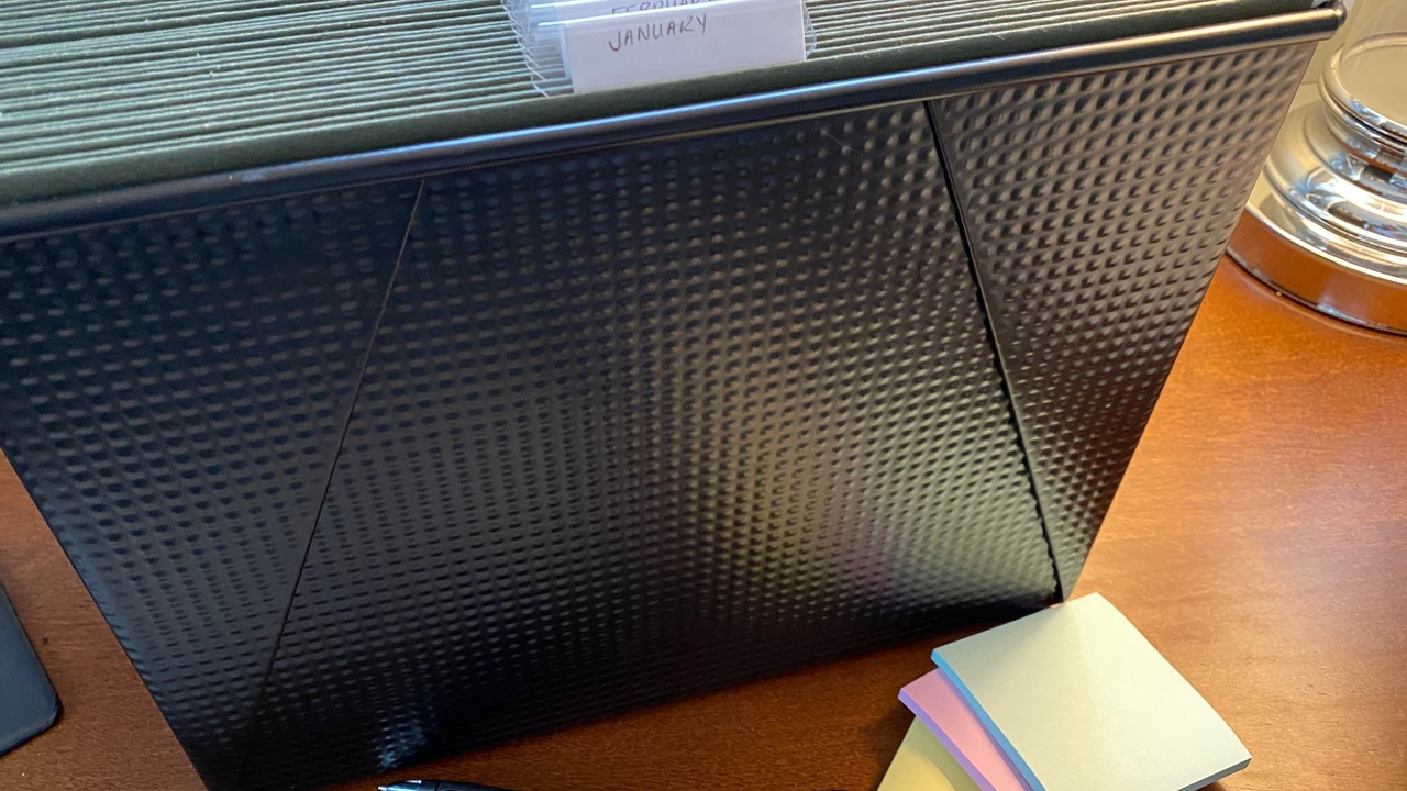 Dark metal file container and pastel post it notes on wood desk for organizing paper clutter.