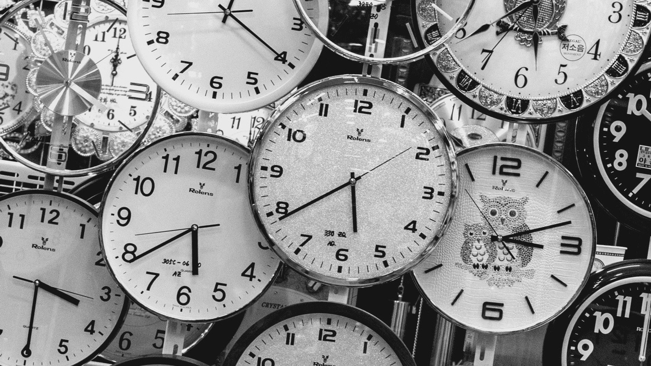 Many clocks black and white all telling time.