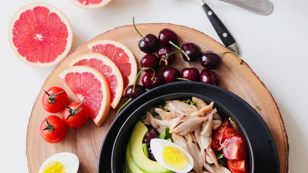 Whole food plate with pink grapefruit, cherries, tomatoes, boiled egg, avocado and lean white chicken meat. Healthy fats and plant based diet.