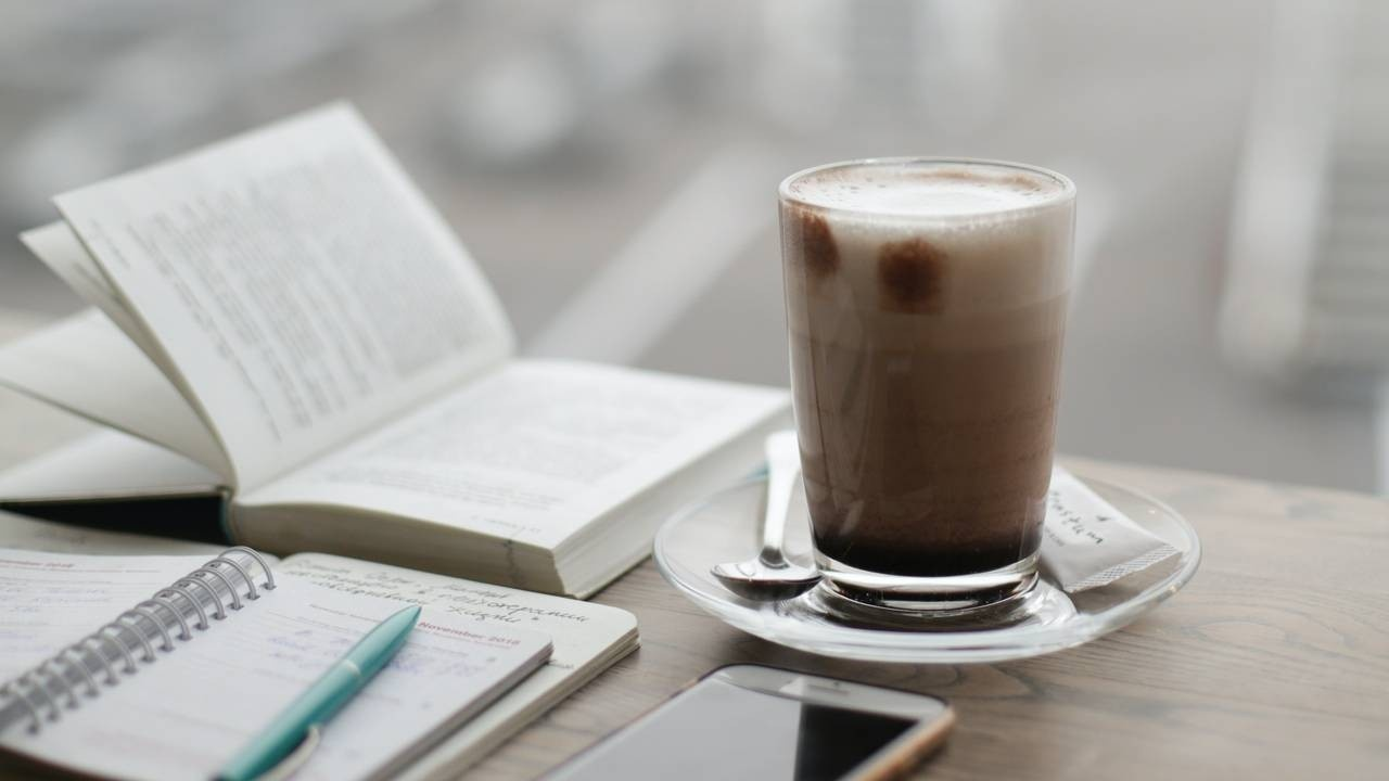 Coffee, cafe, latte, cappuccino, foam, clear glass cup, journal, pen, phone, book, morning routine.