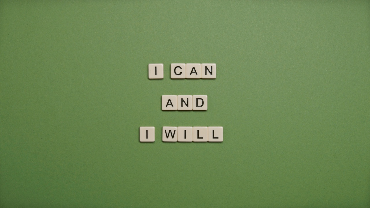 Green background with scrabble tiles spelling, I can and I will.