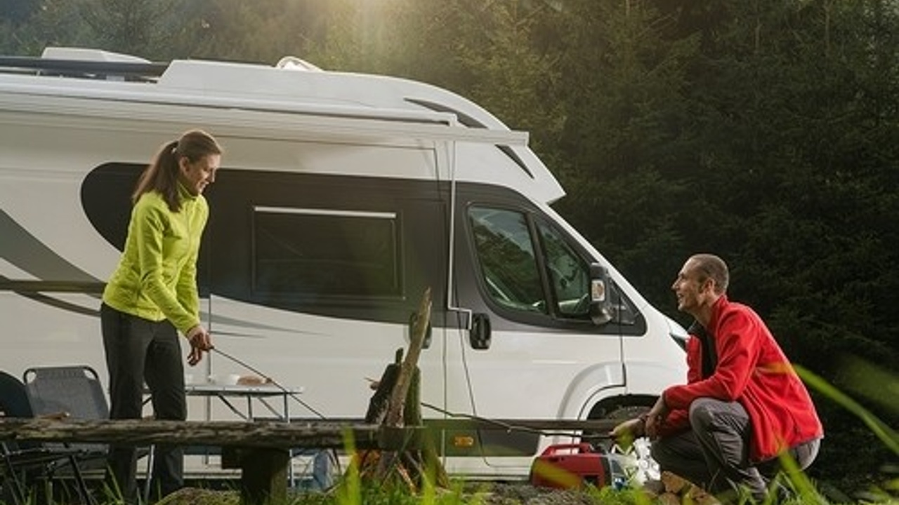 Man and woman camping outside RV