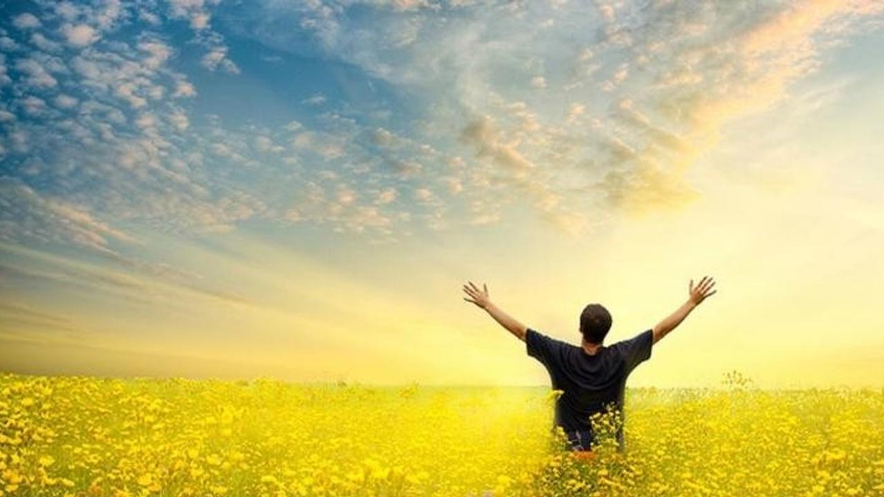 Homme à bras ouvert dans la mer faisans face au ciel
