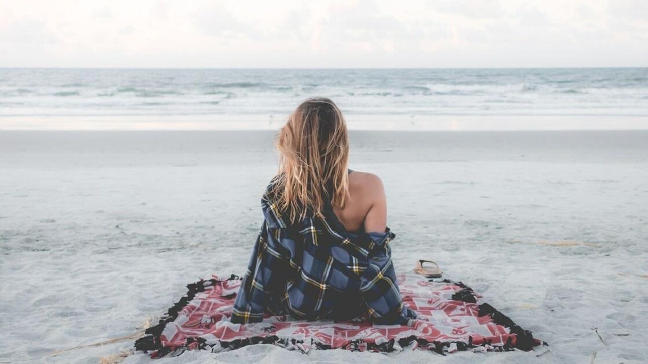 Femme assise sur une couverture sur la plage regardant la mer devant