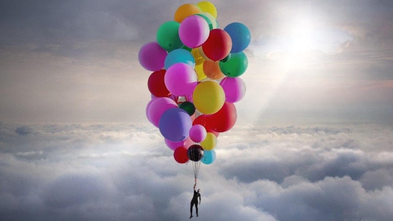Homme soulevé au-delà des nuages par un paquet de ballounes