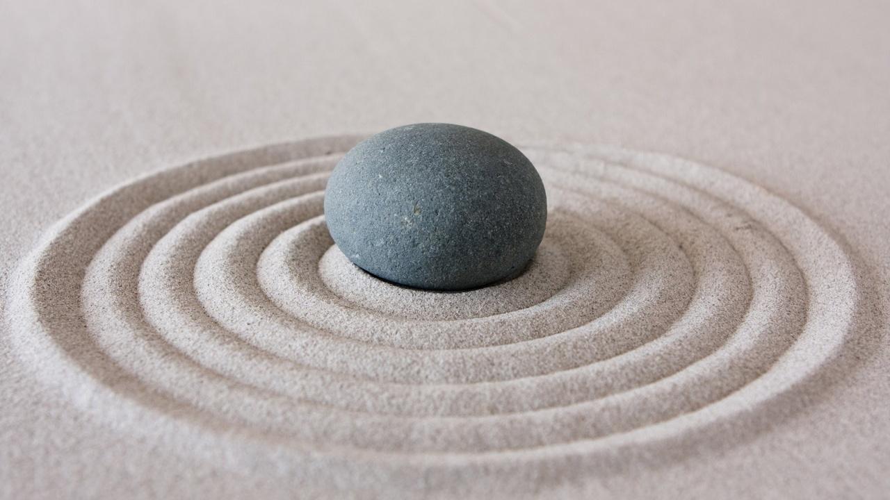 Petite pierre dans le sable avec des cercles tracés autour comme des vagues dans le sable
