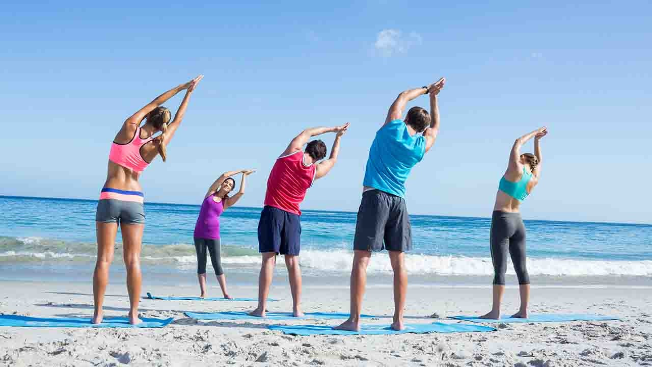 group stretching on the beach