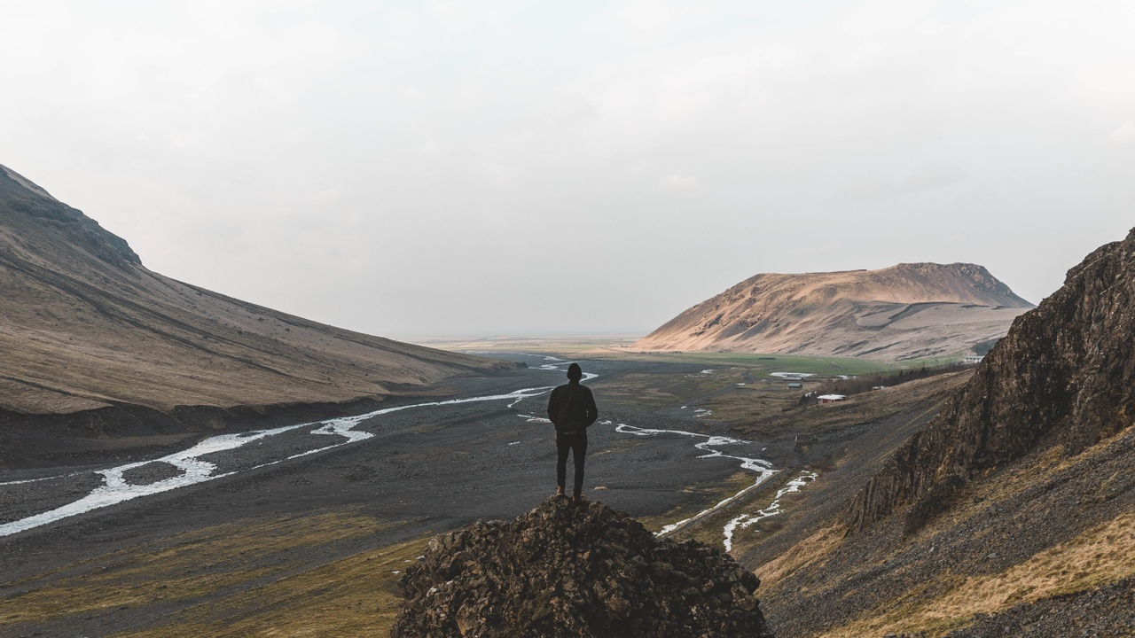 Man on mountain contemplating if he's good enough