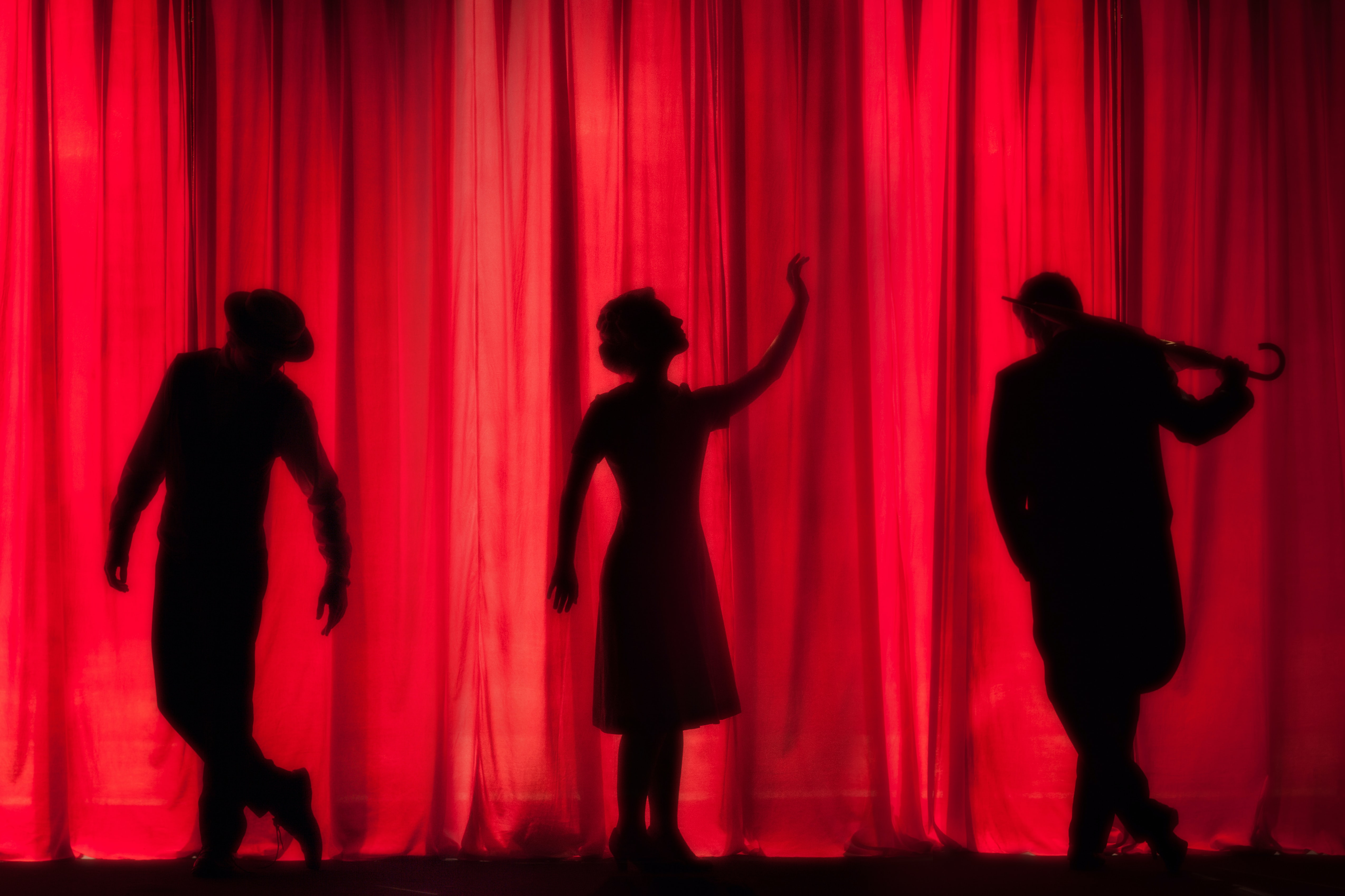 Silhouette of three stage actors behind a red curtain