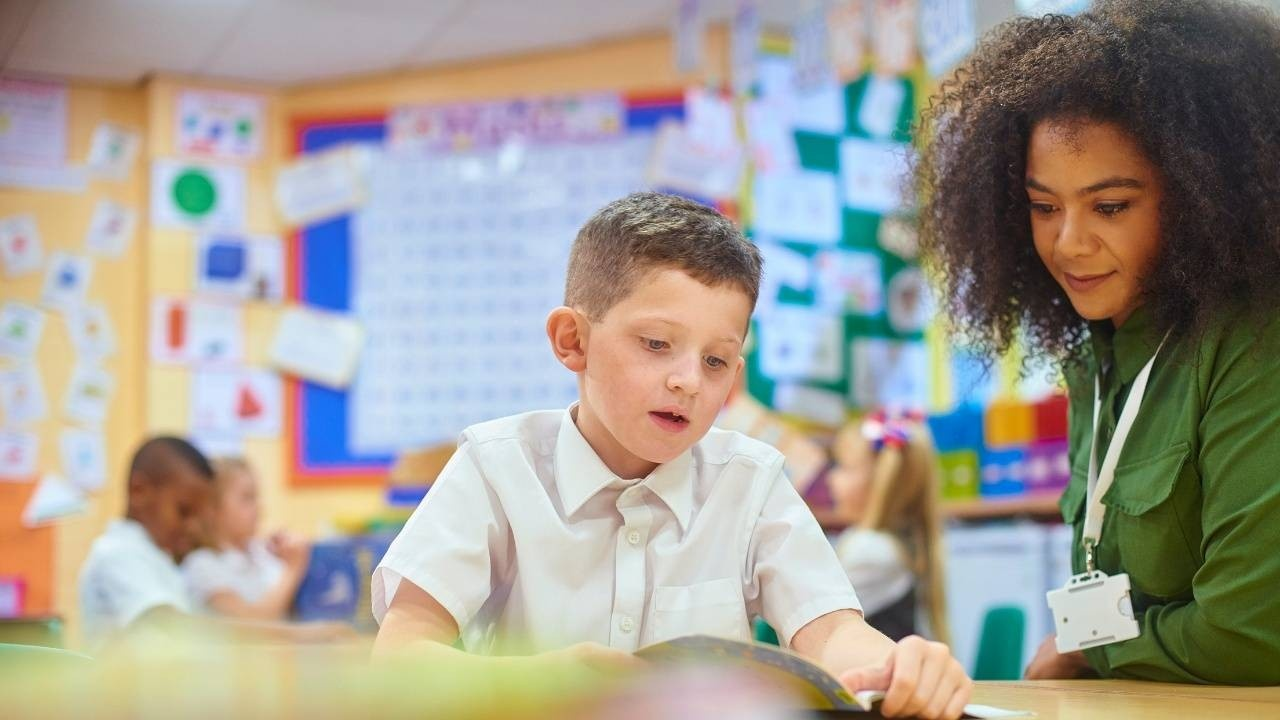 A literacy instructor works 1:1 with a student in a bright and friendly classroom.