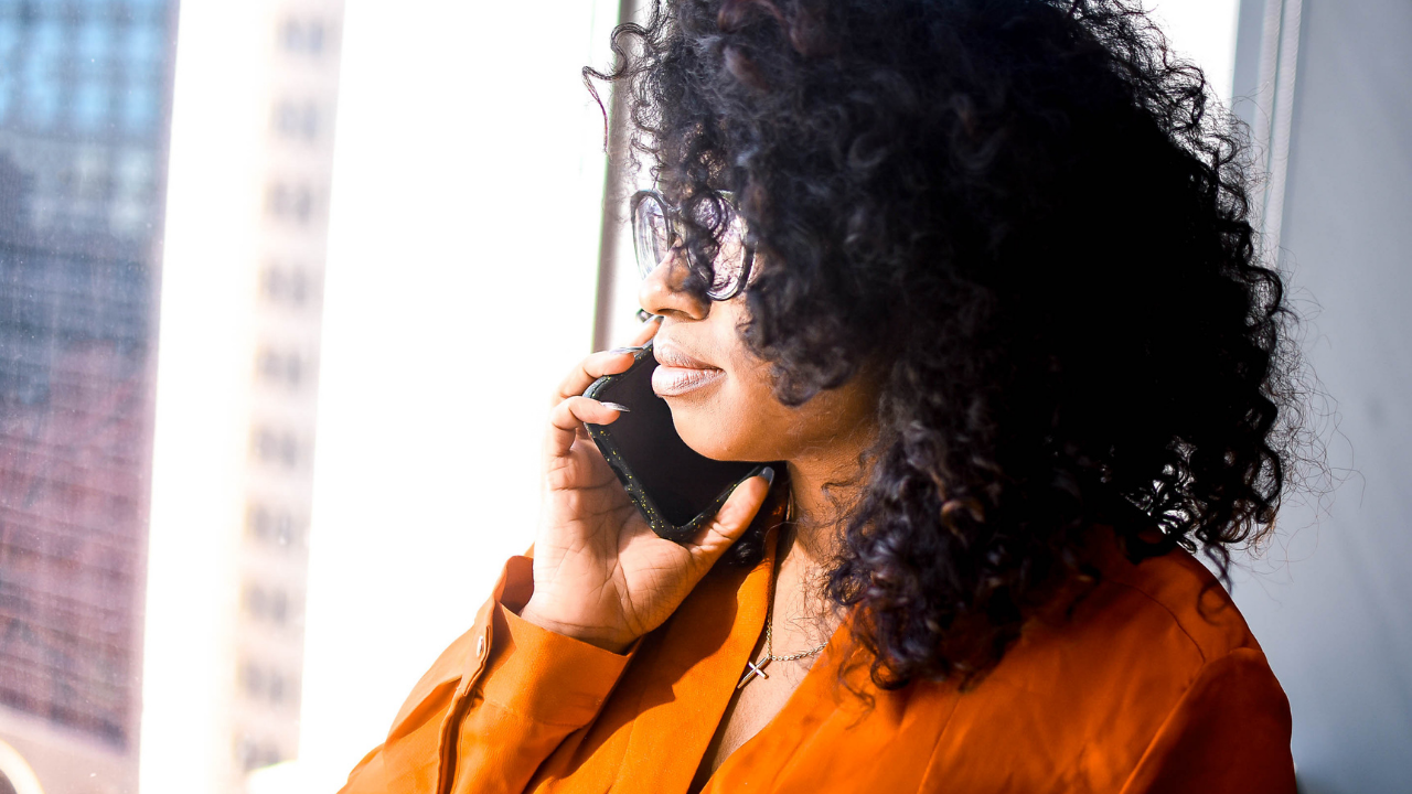 Black woman with curly black hair in a copper colored shirt stares out of a window while holding a cellphone to her right ear