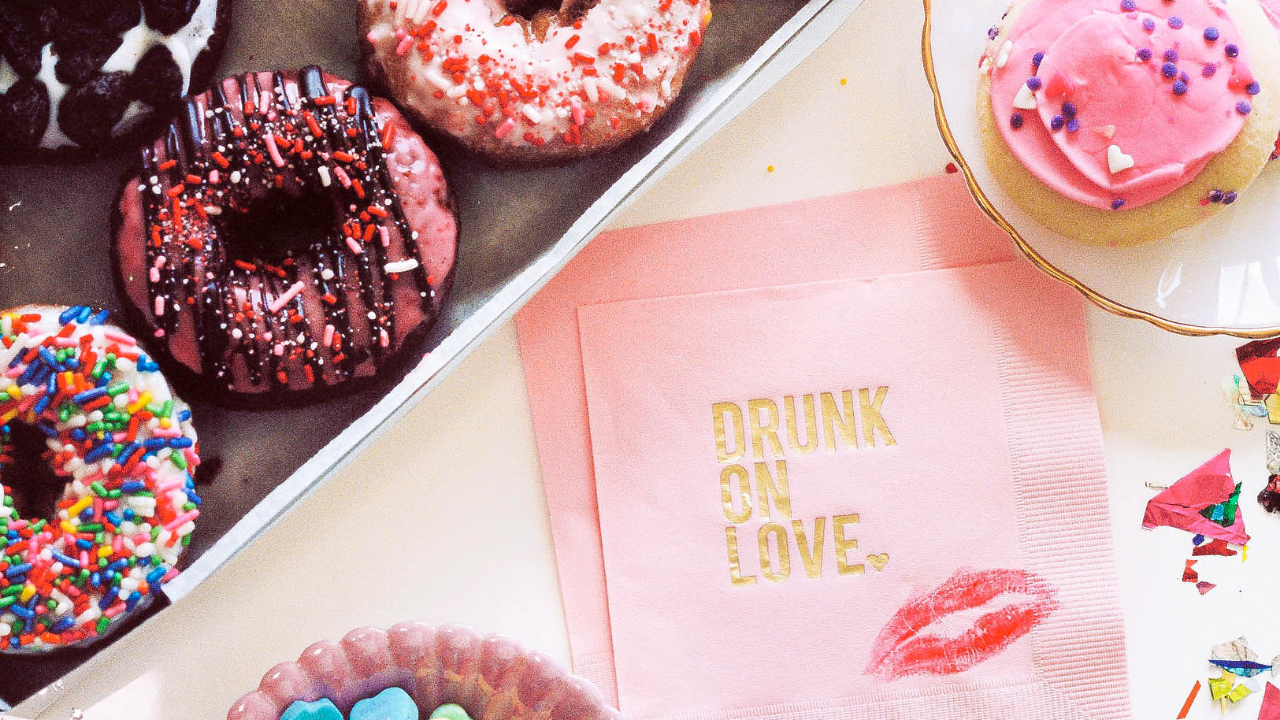 Gray tray of donuts, a doughnut on a small plate and a napkin saying Drunk On Love with a lipstick smear