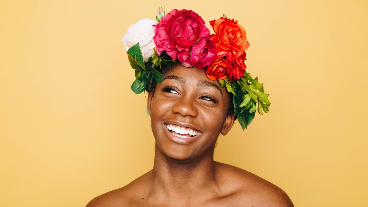 Woman with flower crown smiling.