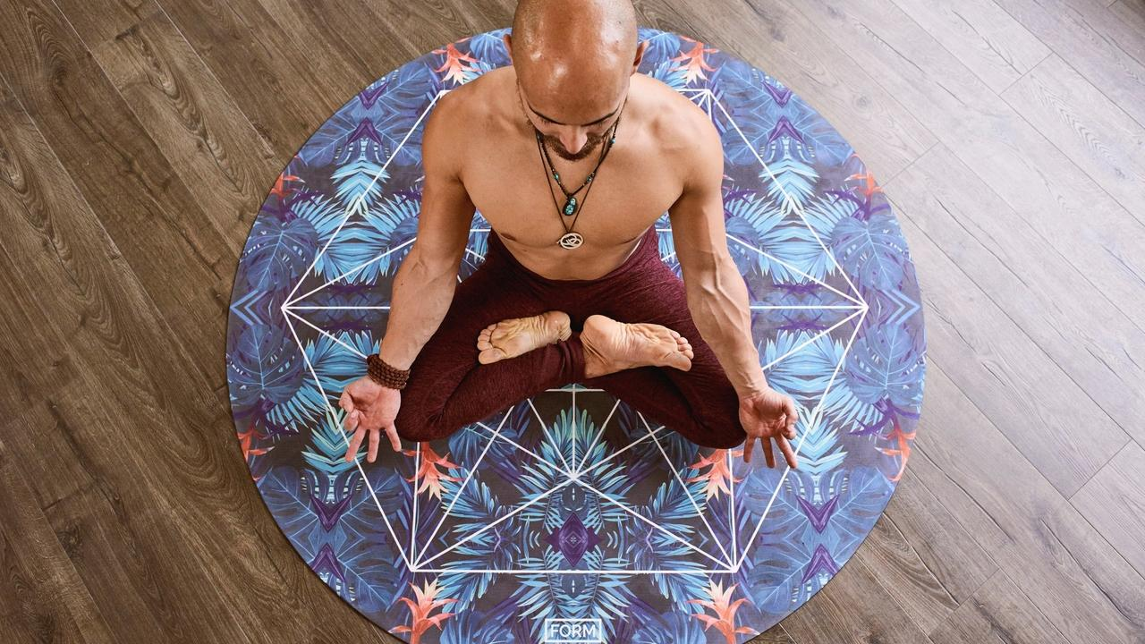 Bald Man sitting on the center of mat Meditating with Become Yoga School logo