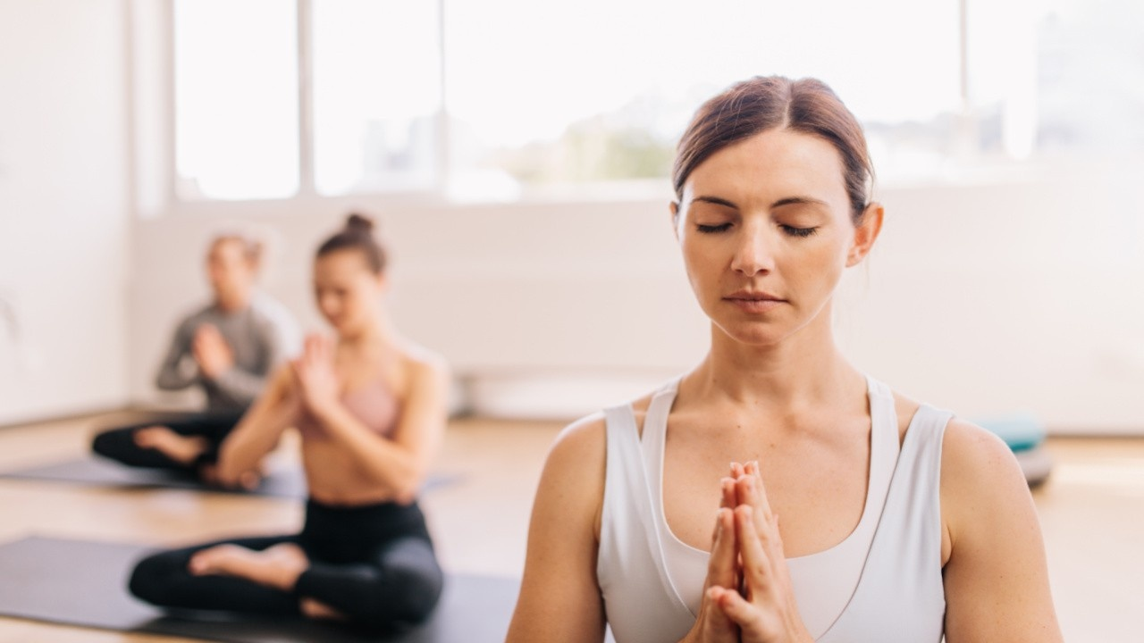 Three Women in Yoga Class with Hands in Prayer Position Namaste Anjali Mudra doing Yoga Teacher Training Course with Become Yoga School