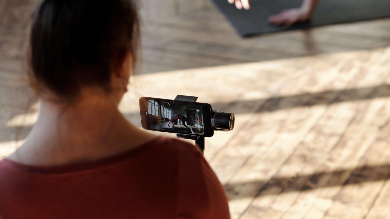 Turned away yoga student holding a camera, recording another co-yogi doing yoga