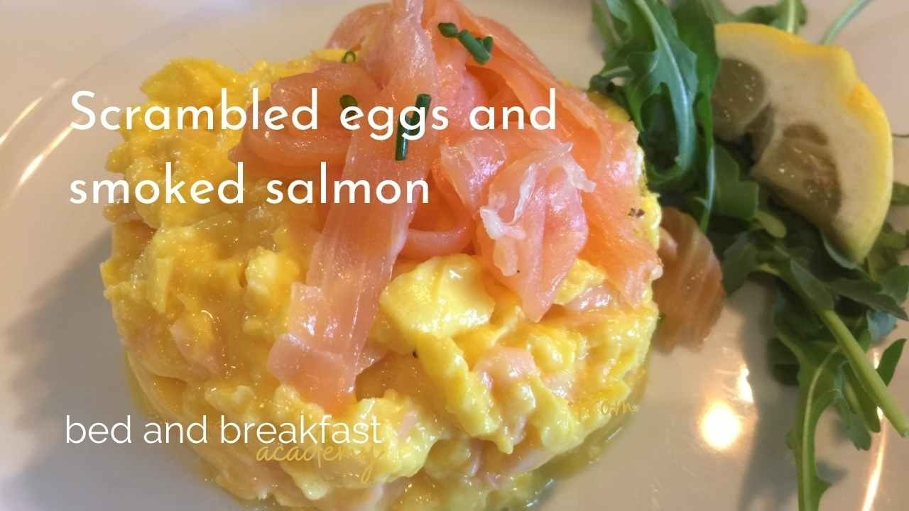 a white plate with scrambled eggs, topped with smoked salmon with a green rocket and lemon garnish