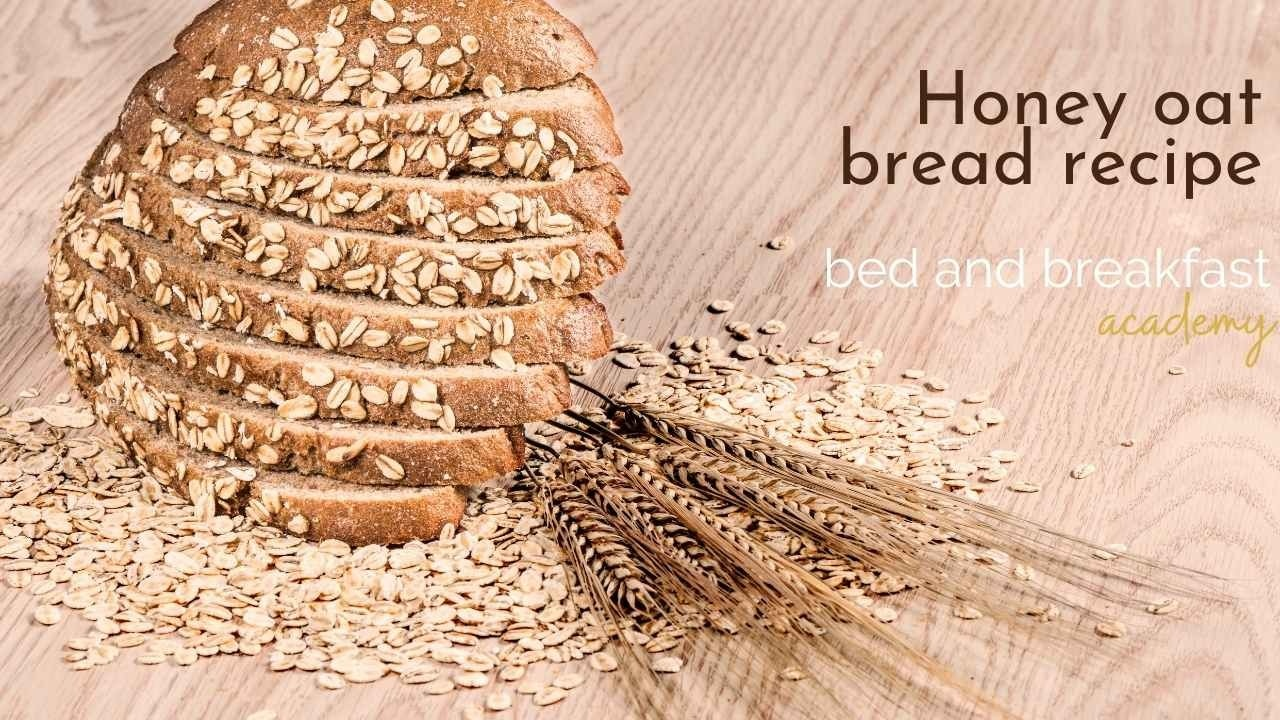 sliced brown bread scattered with whole oats on a wooden board covered in oats