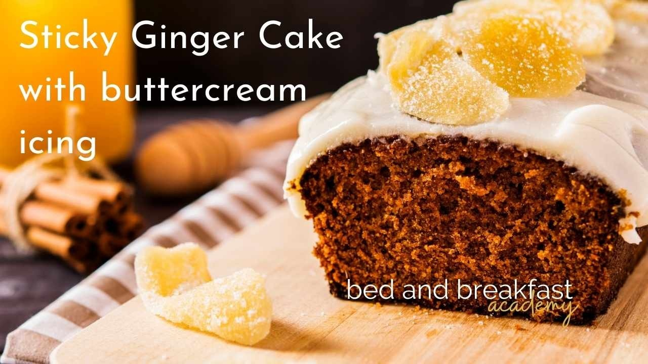 ginger loaf with butter icing on a wooden chopping board on a brown and white check cloth