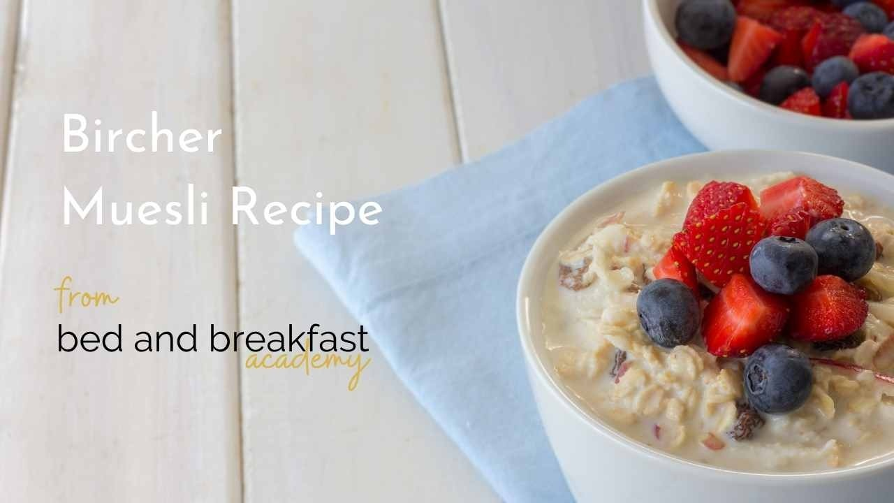 White bowl of bircher muesli with strawberries and blueberries on a blue napkin on a white wooden table