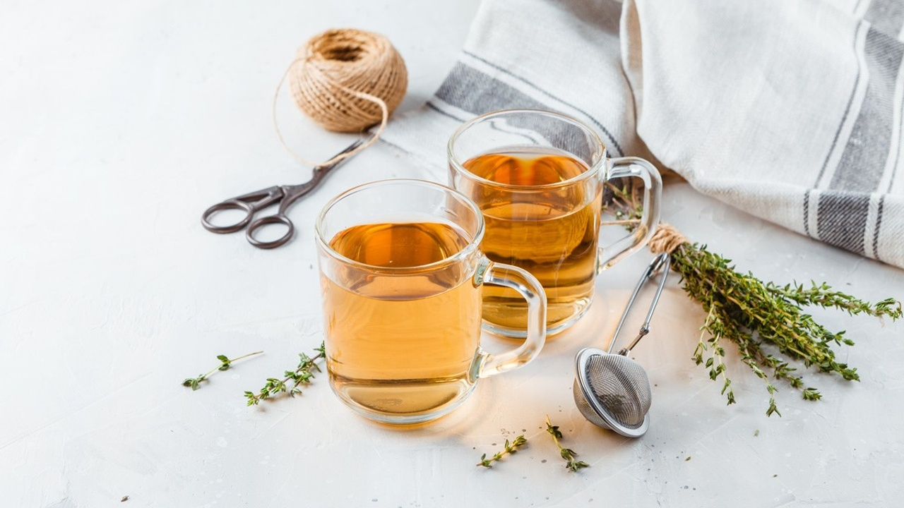 Two glass cups of tea with herbs, a tea steeper, scissors, and a kitchen towel on a white countertop.