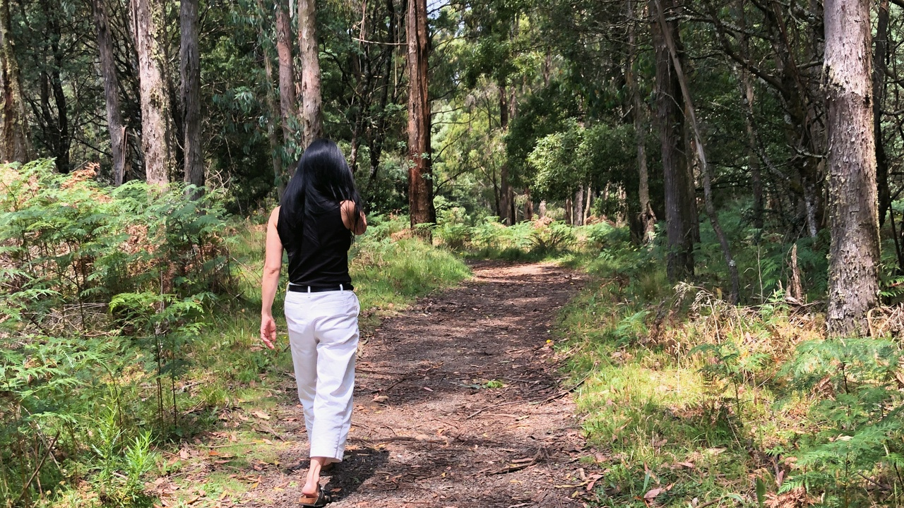 Image of an East Asian woman walking amongst nature.