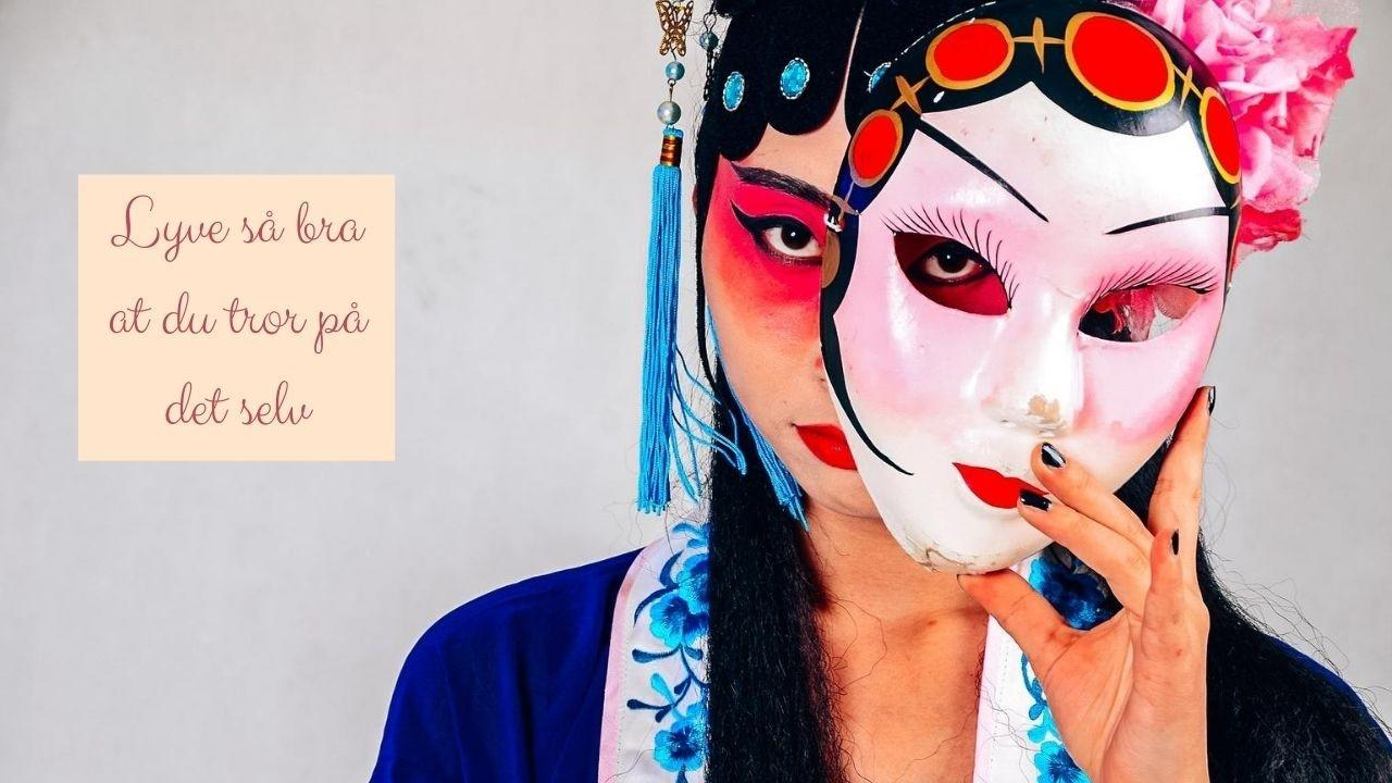 Dame (kvinne) som gjemmer seg bak en maske.