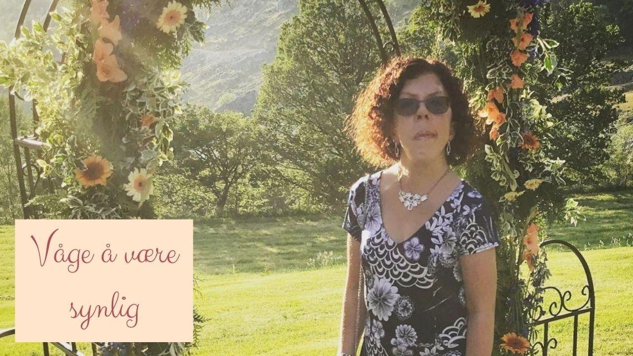 Linn Kleppa i bryllup, med blå kjole med hvitt blomstermønster. Står ved en portal med mange fine blomster i nydelige farger. Solen skinner.