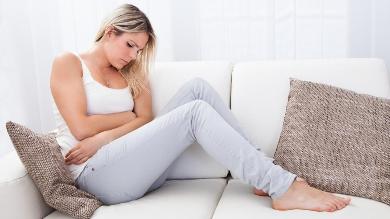 woman on a couch with stomach pain