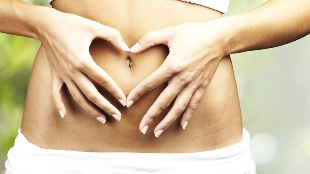 woman making a heart with her hands on her belly
