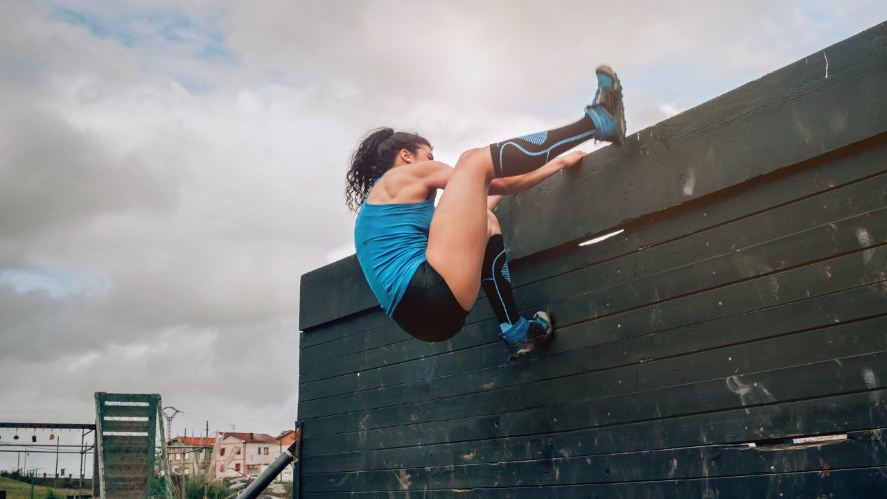 Strong young lady climbing up a wall showing strength