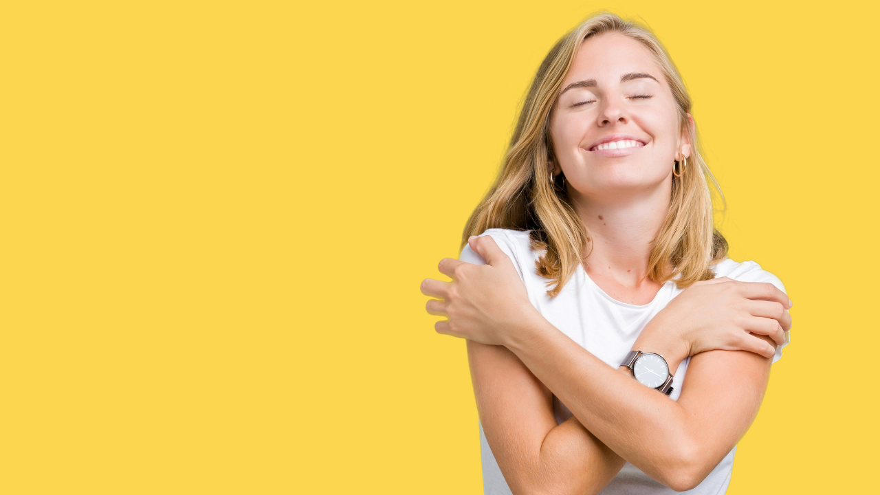 Young woman expressing self-love with a hug