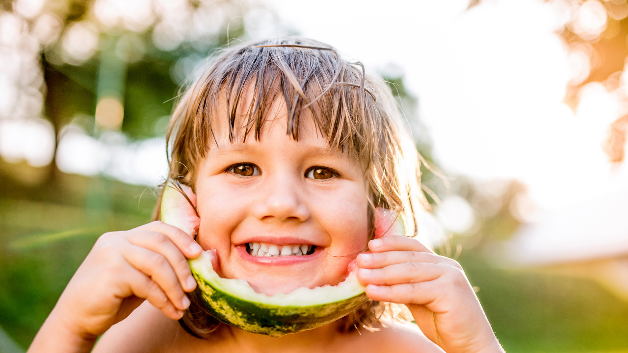 Little boy with a big smile and watermelon on his face
