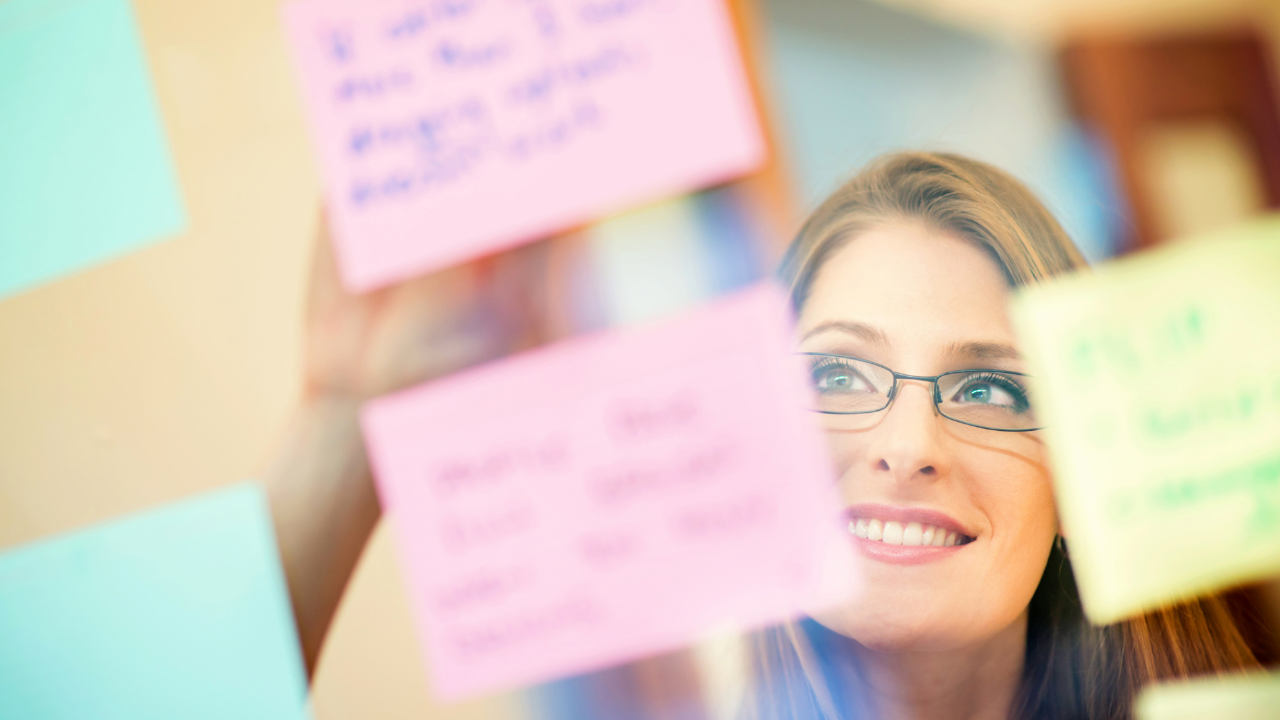 Woman in glasses with post-it notes all around clarifying goals