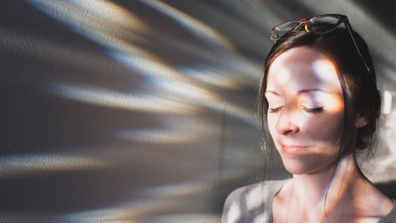 Calm and composed young woman with eyes closed in front of light reflections