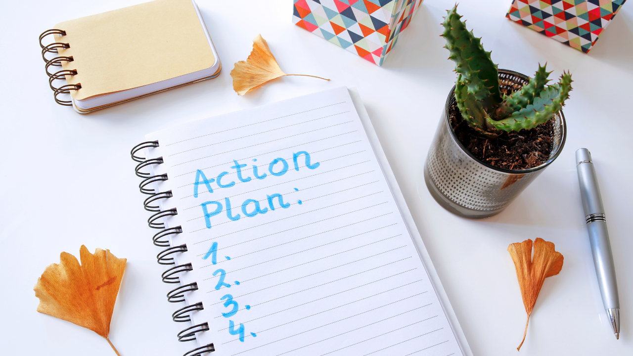 Organized desk with plants and notebook to write action plan