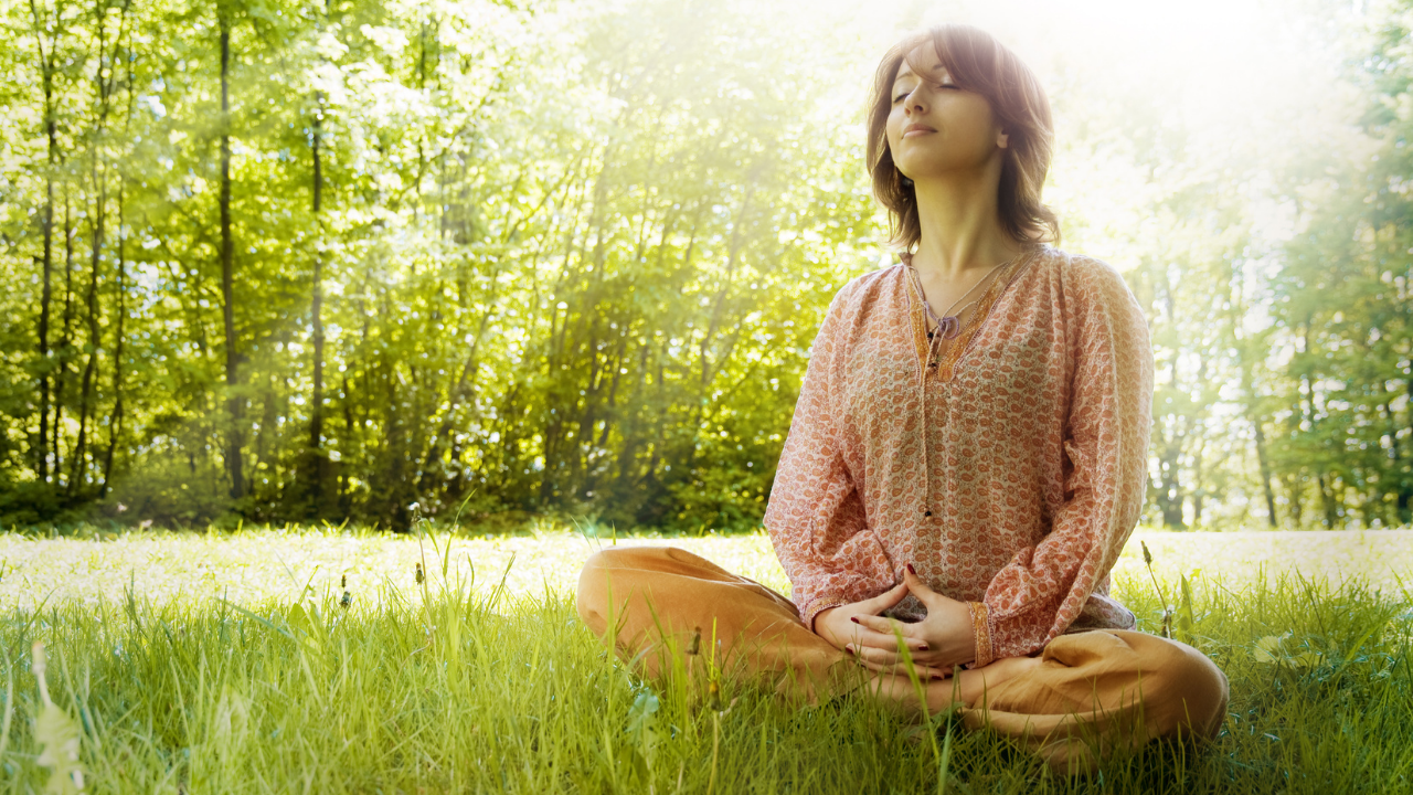Young woman sitting on the grass, meditating.