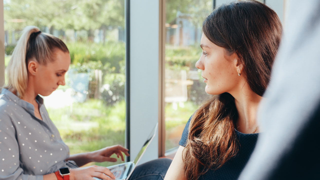 Envious woman looking at another woman focused on her laptop