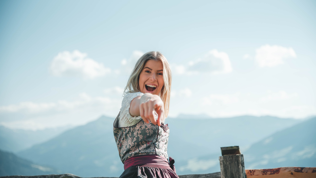 Blonde woman in nature pointing at camera