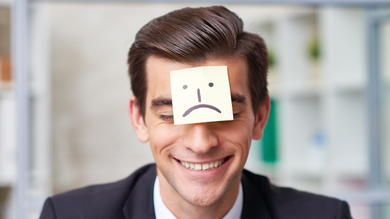 Sad face post-it note on smiling man's forehead